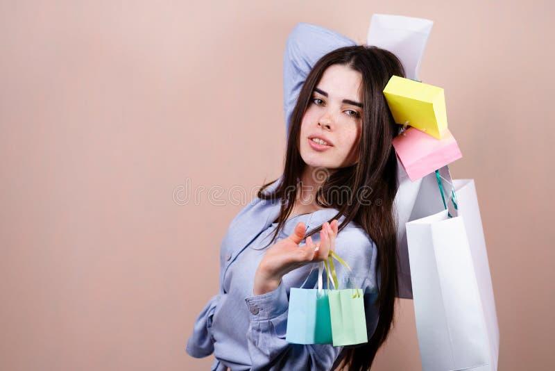 Lycklig kvinna som rymmer m?nga shoppa p?sar med gods arkivbild