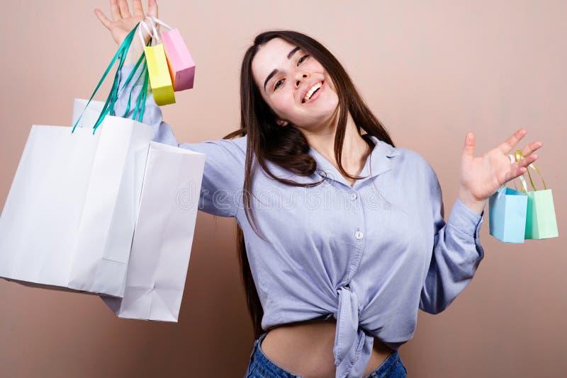 Lycklig kvinna som rymmer m?nga shoppa p?sar med gods royaltyfri bild