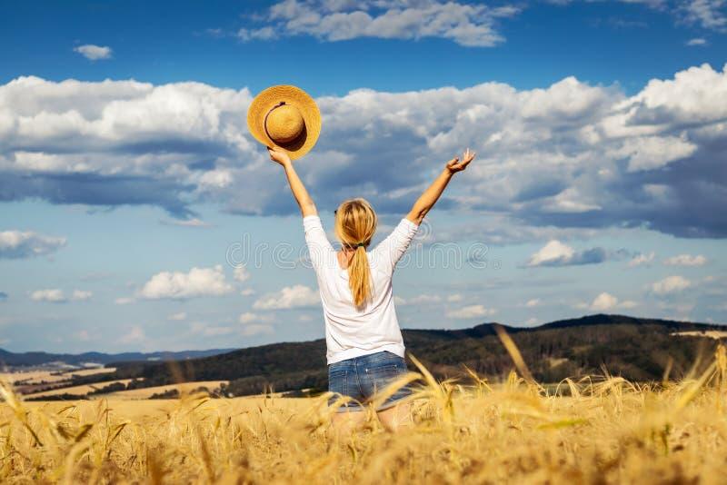 Lycklig kvinna som rymmer sugrörhatten med handen som lyfts i vetefält Njutning av sommar royaltyfri foto