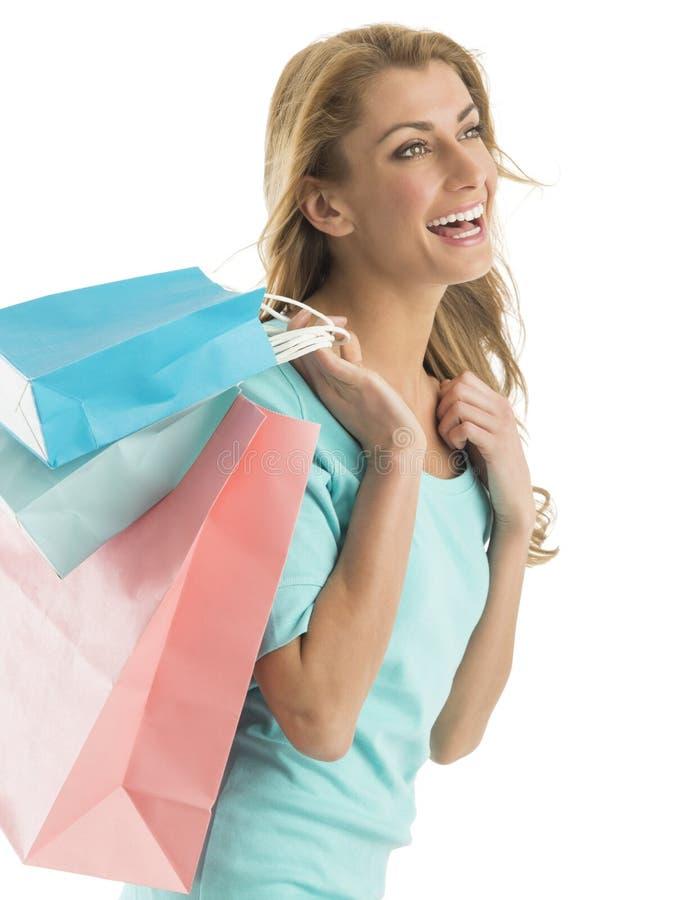 Lycklig kvinna som ser bort, medan bära shoppingpåsar royaltyfria foton
