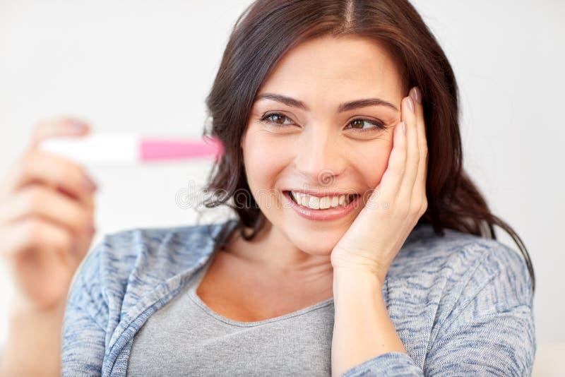 Lycklig kvinna som ser den hemmastadda graviditetstestet royaltyfri bild