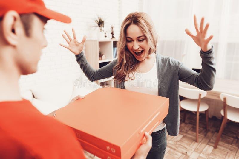 Lycklig kvinna som ser den pizzaasken och kuriren royaltyfria bilder