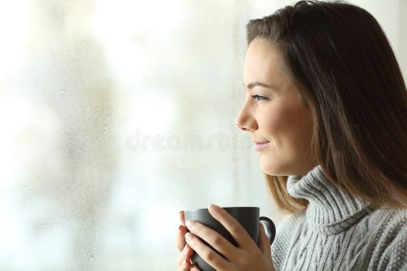 Lycklig kvinna som ser för att regna rymma kaffe till och med fönstret arkivbild