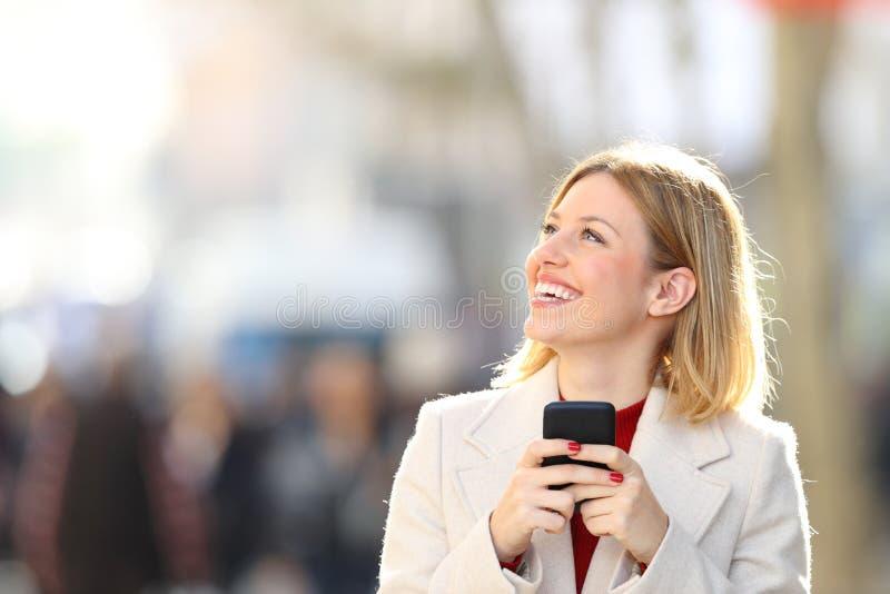 Lycklig kvinna som ser sidoinnehavtelefonen i gatan royaltyfri foto