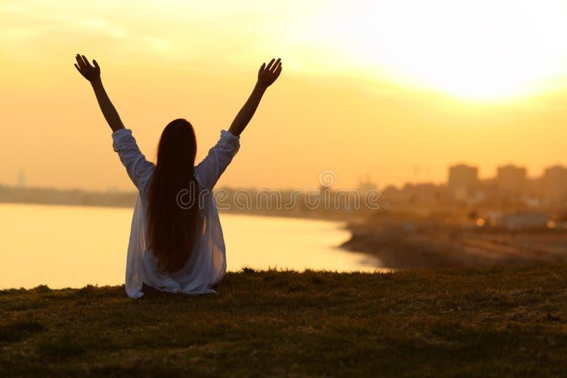 Lycklig kvinna som ser staden på solnedgången och lyfter armar royaltyfri bild