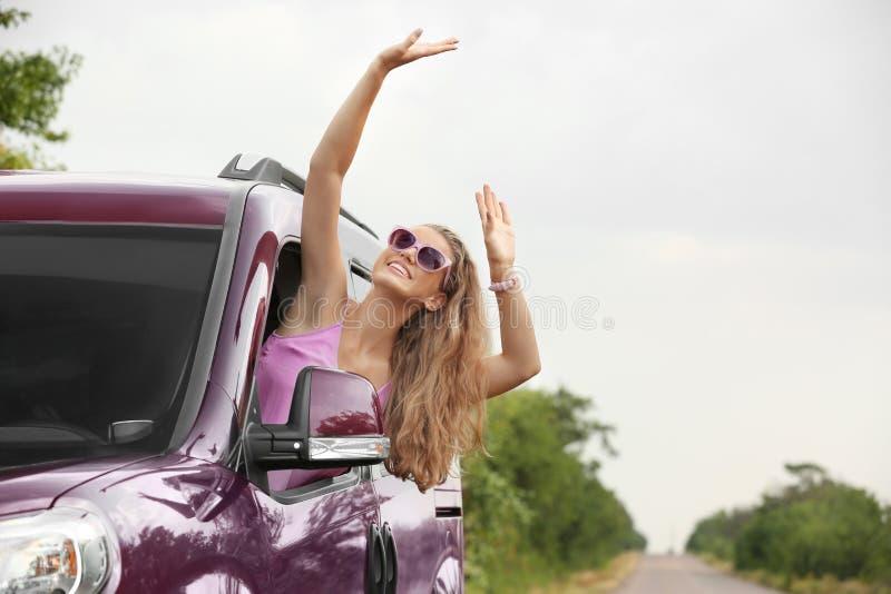 Lycklig kvinna som ser ut ur bilfönster, medan resa arkivfoton