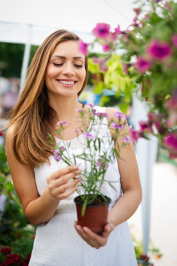 Lycklig kvinna som shoppar härliga blommor i trädgårdmitt fotografering för bildbyråer