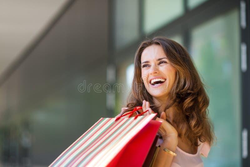 Lycklig kvinna som shoppar ut, hållande övre färgglade shoppingpåsar royaltyfria foton