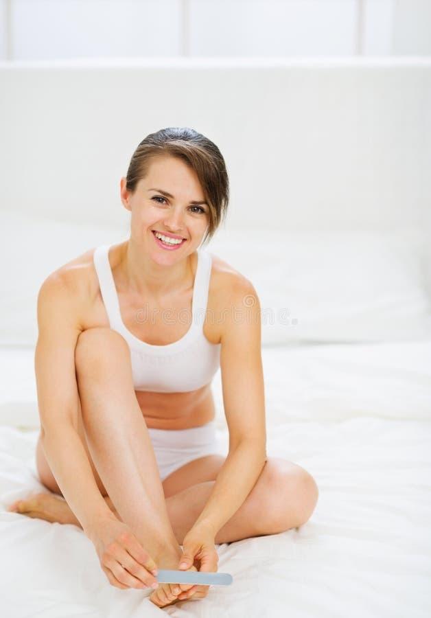 Lycklig kvinna som sitter på underlag och gör manicuren arkivfoton