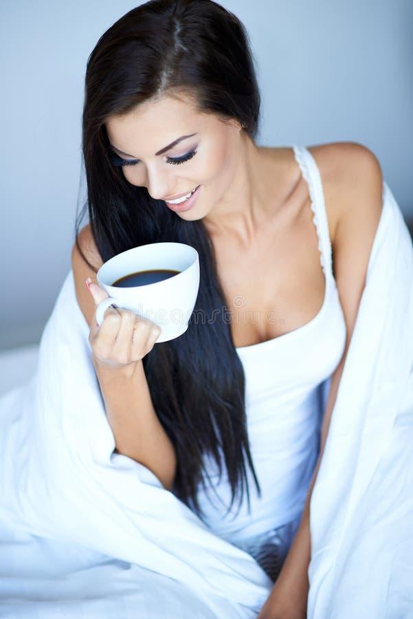 Lycklig kvinna som slås in i filt med koppen kaffe arkivbilder