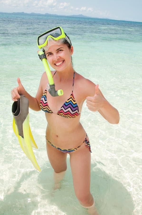 Lycklig kvinna som snorklar och har gyckel i hållande fena för vatten royaltyfri foto