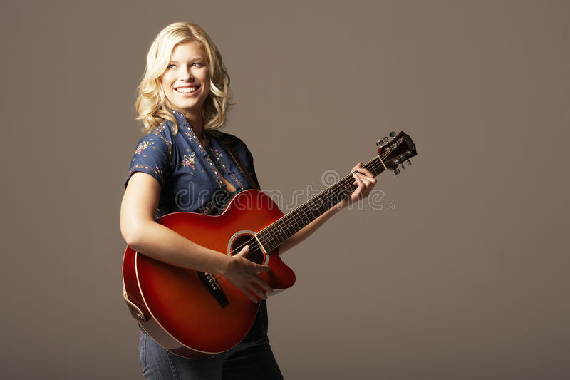 Lycklig kvinna som spelar gitarren arkivfoto