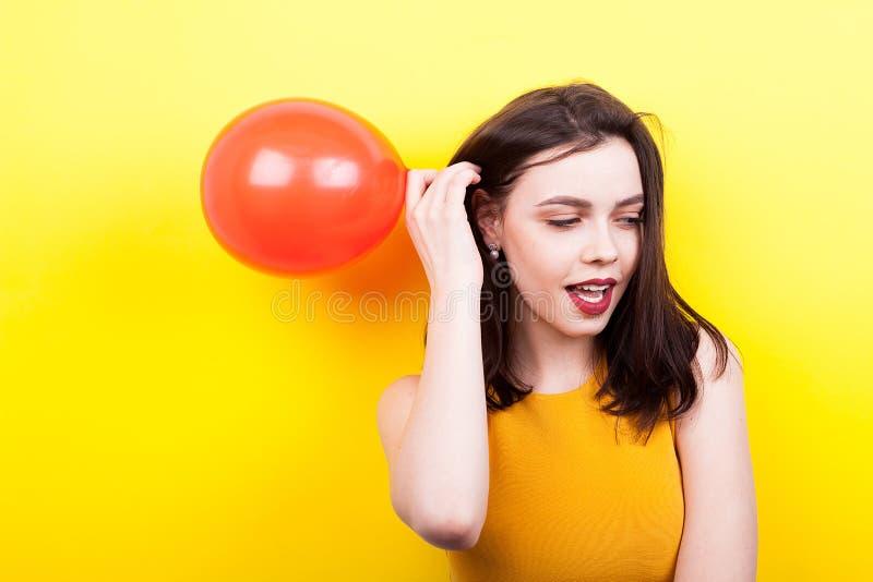 Lycklig kvinna som spelar med en röd ballong royaltyfri bild