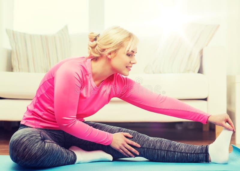 Lycklig kvinna som sträcker benet på mattt hemmastatt royaltyfri foto