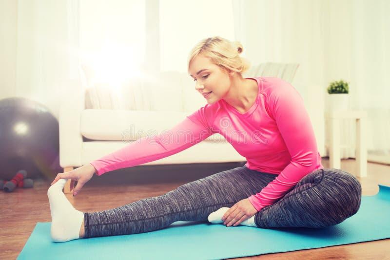 Lycklig kvinna som sträcker benet på mattt hemmastatt arkivfoton