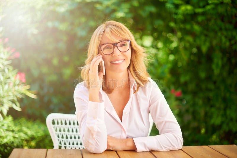 Lycklig kvinna som talar med något på hennes mobiltelefon arkivfoton