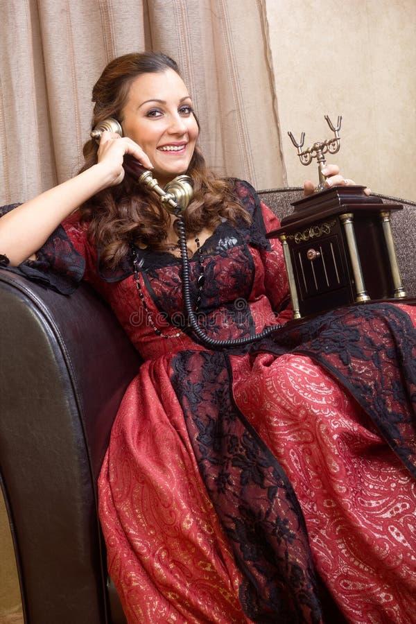 Lycklig kvinna som talar på den retro telefonen royaltyfri bild