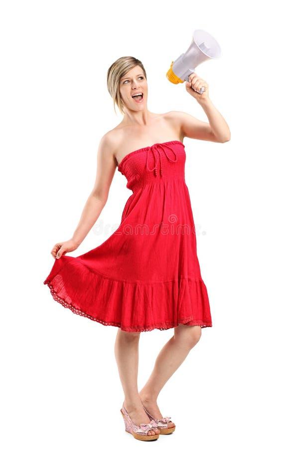 Lycklig kvinna som talar på en megafon arkivfoto