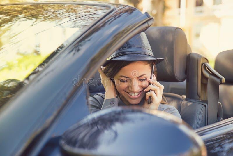 Lycklig kvinna som talar på telefonen i bil royaltyfri foto