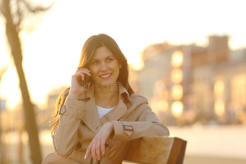 Lycklig kvinna som talar på telefonen som sitter på solnedgången royaltyfri foto