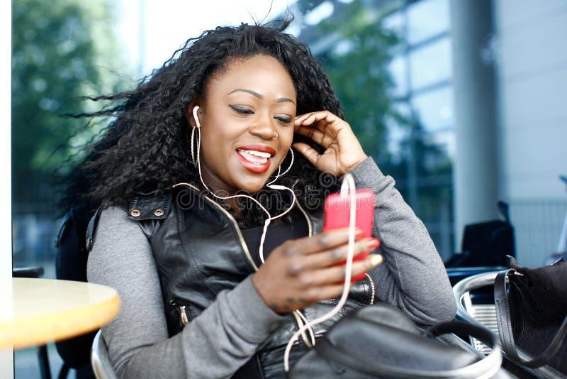 Lycklig kvinna som talar till och med telefonen och headphonen arkivbilder