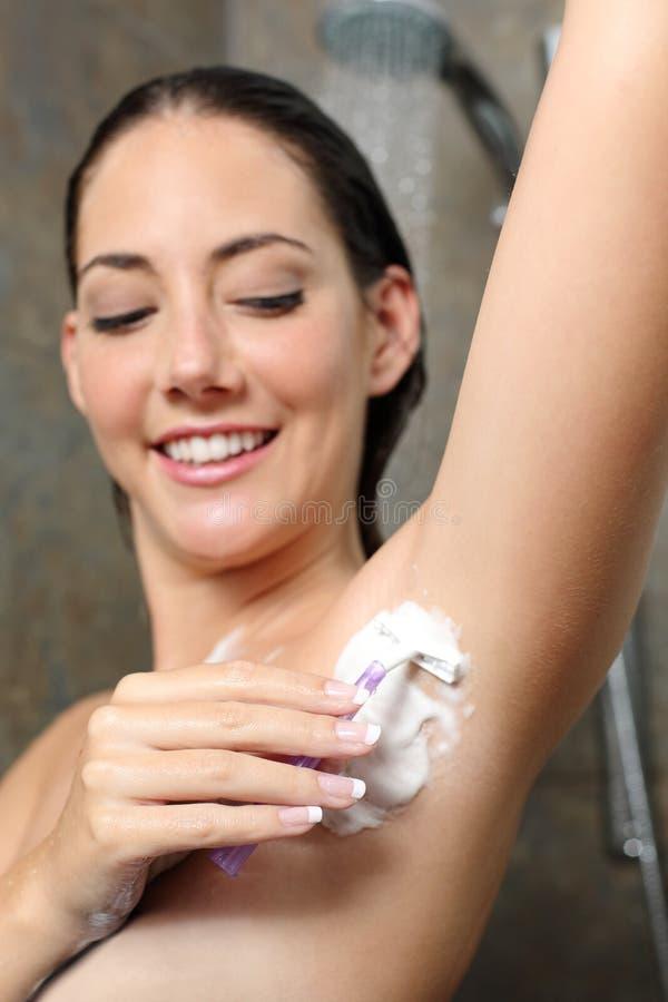 Lycklig kvinna som tar bort armhålahår i duschen fotografering för bildbyråer