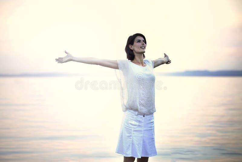 Lycklig kvinna som tar en djup andedräkt på solnedgången royaltyfria foton