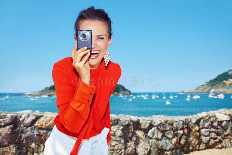Lycklig kvinna som tar fotoet med den digitala kameran som är främst av lagun arkivbild