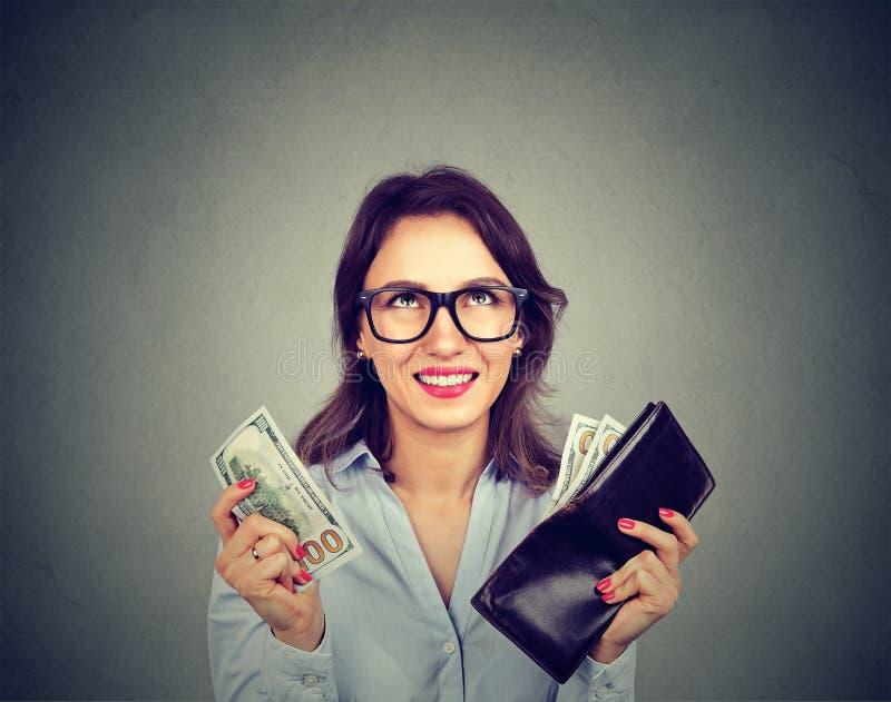 Lycklig kvinna som tar pengar ut ur plånboken arkivfoto