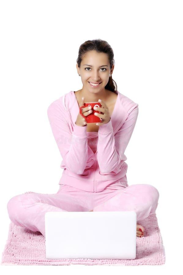 Lycklig kvinna som tillbaka ser med bärbar dator arkivfoto