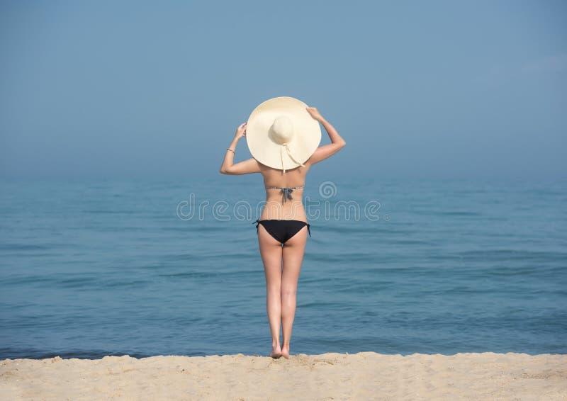 Lycklig kvinna som tycker om att koppla av för strand som är glat i sommar vid blått vatten royaltyfri bild