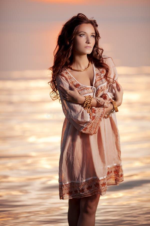 Lycklig kvinna som tycker om i havssolnedgång fotografering för bildbyråer