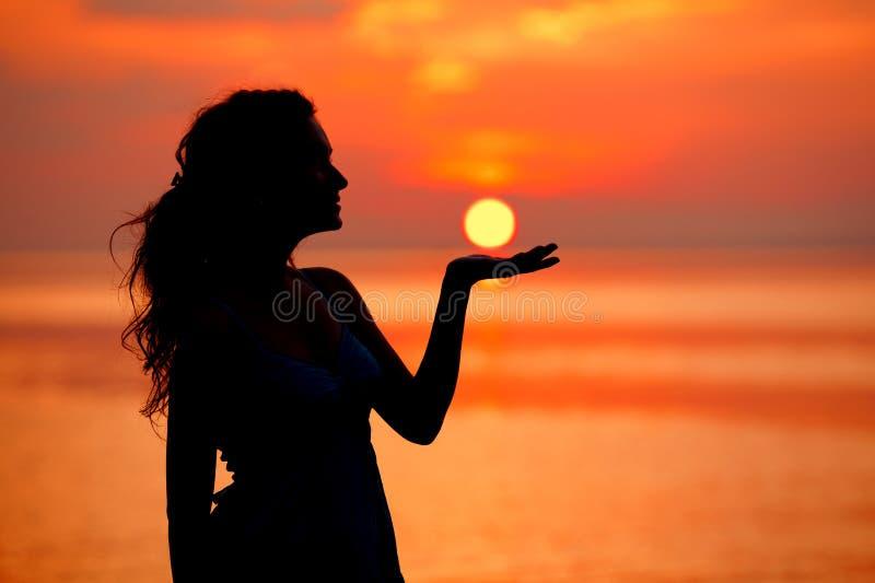 Lycklig kvinna som tycker om i havssolnedgång Silhouetted mot solarna royaltyfri foto