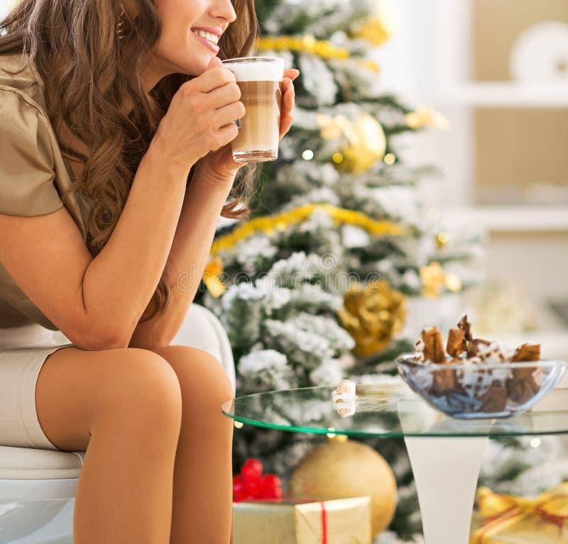 Lycklig kvinna som tycker om lattemacchiato nära julträd arkivbild