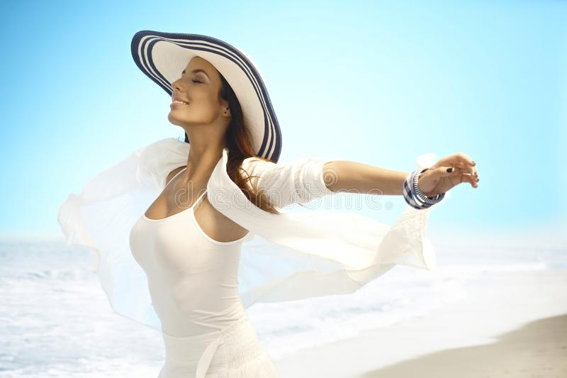 Lycklig kvinna som tycker om sommarsolen på stranden