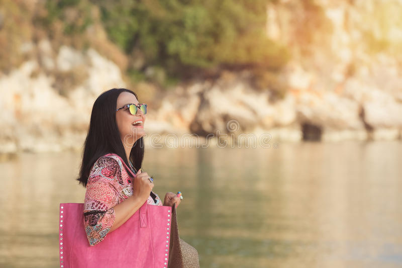 Lycklig kvinna som tycker om stranden och morgonsolen royaltyfri fotografi