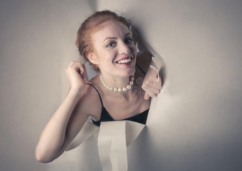 Lycklig kvinna som ut poppar från en papp royaltyfria bilder