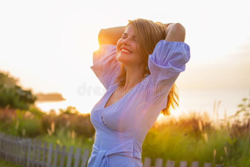 Lycklig kvinna som utomhus tycker om liv på solnedgången royaltyfria bilder