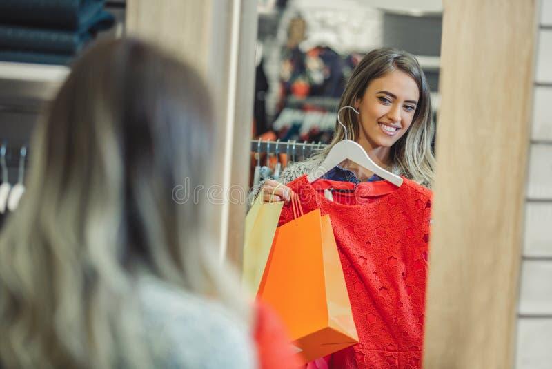 Lycklig kvinna som väljer kläder och ser för att avspegla i lager fotografering för bildbyråer