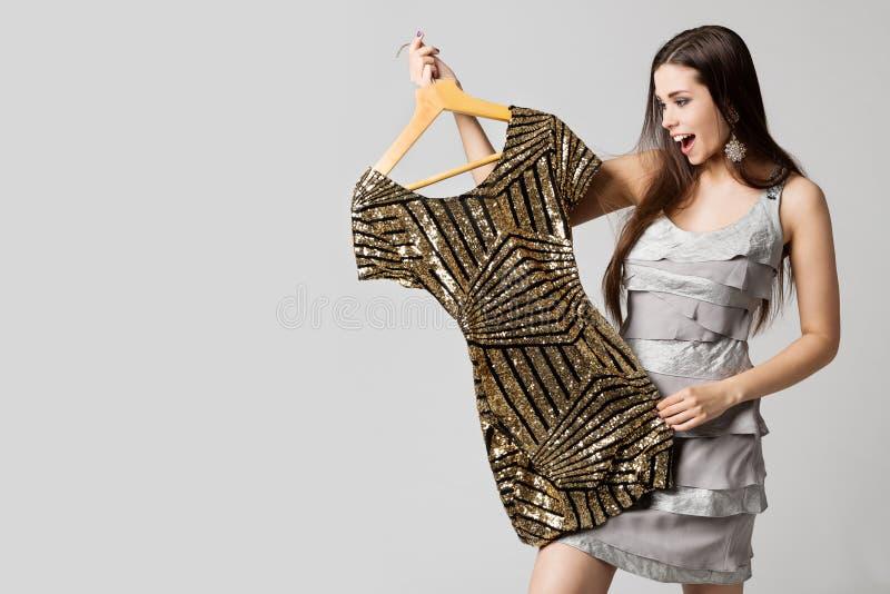 Lycklig kvinna som väljer klänningen, attraktiv flicka som rymmer guld- kläder på hängare på vit arkivfoto
