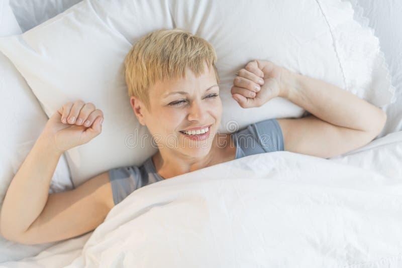 Lycklig kvinna som vaknar upp i säng royaltyfria foton