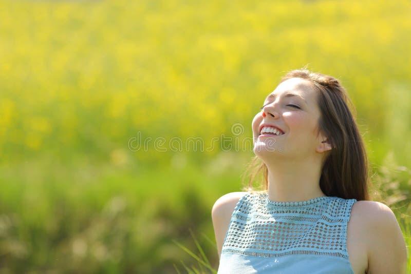 Lycklig kvinna som vilar andas ny luft i ett fält arkivbilder
