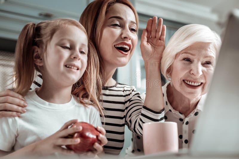Lycklig kvinna som vinkar, medan sitta med släktingar och ha den videopd appellen arkivfoton