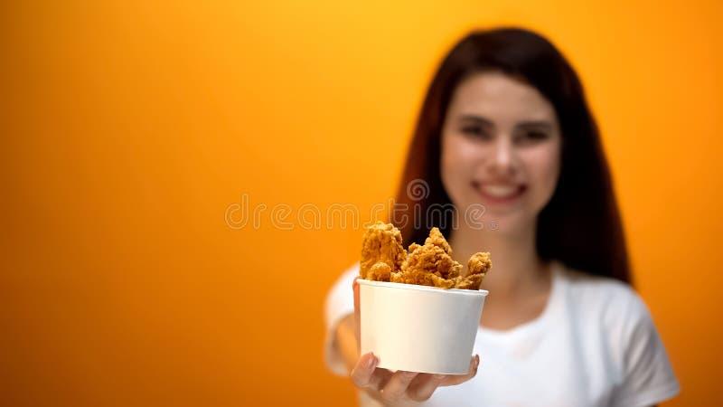 Lycklig kvinna som visar läcker men sjuklig skräpmat för grillade fega vingar, royaltyfri foto