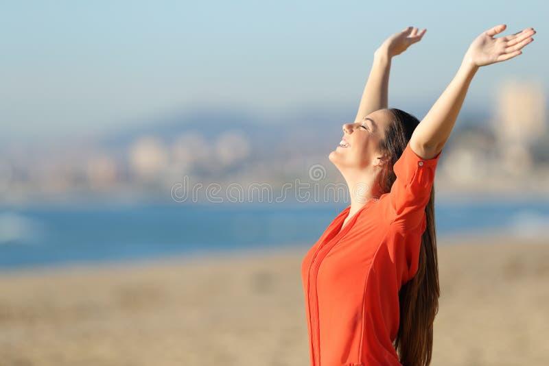 Lycklig kvinnaandning och lyftaarmar på stranden arkivbilder