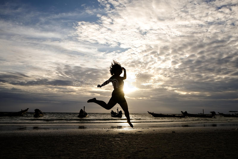 Lycklig kvinnabanhoppning i havssolnedgång royaltyfri foto