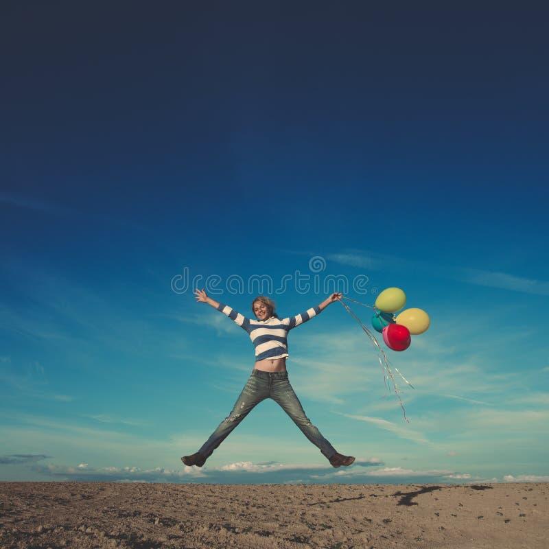 Lycklig kvinnabanhoppning med födelsedagballonger royaltyfria bilder