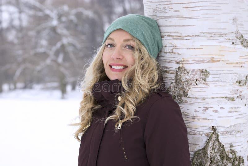 Lycklig kvinnabenägenhet mot träd i vinter royaltyfri foto