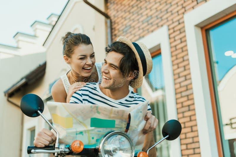 Lycklig kvinnabenägenhet på man med översikten i händer, medan sitta på den retro sparkcykeln arkivfoton