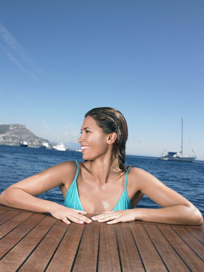 Lycklig kvinnabenägenhet på yachts golvtilja i havet arkivbilder